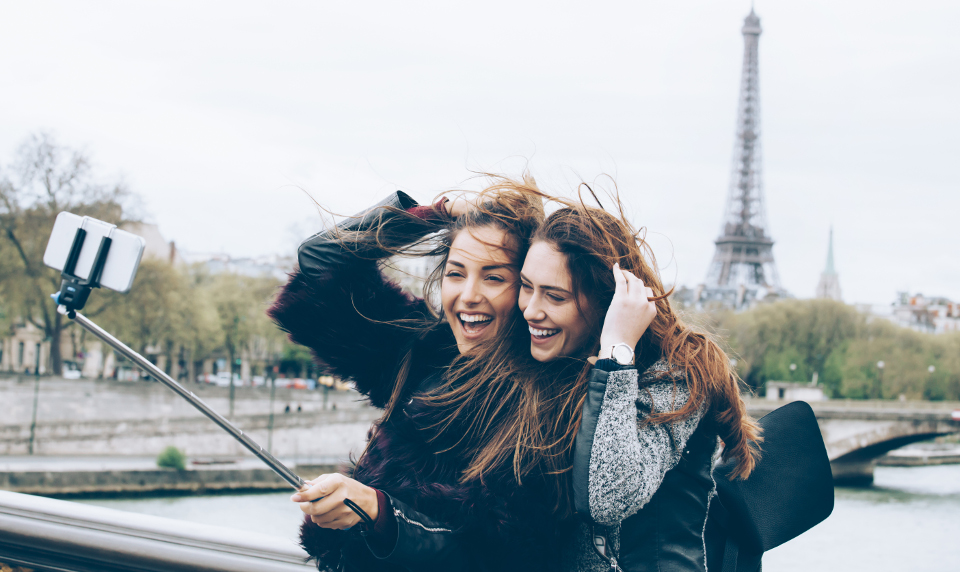 Two female students taking a photo in front of the Eiffel Tower