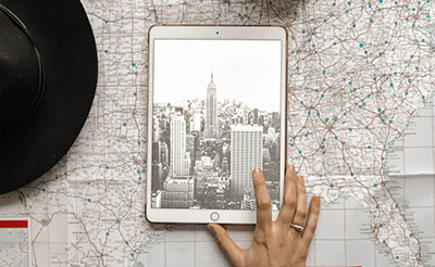 A hand uses an iPad that sits on a map of America