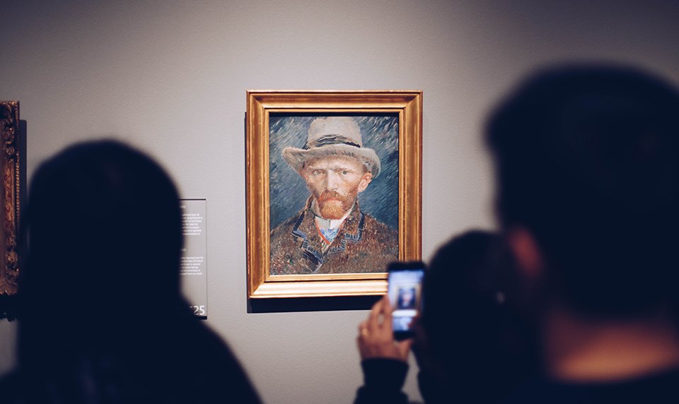 Museum visitors observe one of Van Gough's self portraits, a classic piece of art history