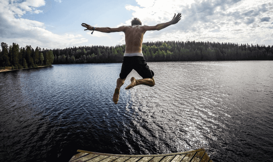 Man in swim trunks jumping into a lake