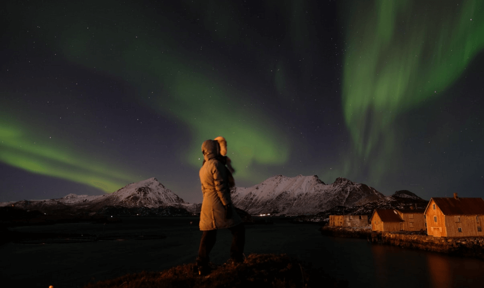 Woman in parka gazing at Northern Lights