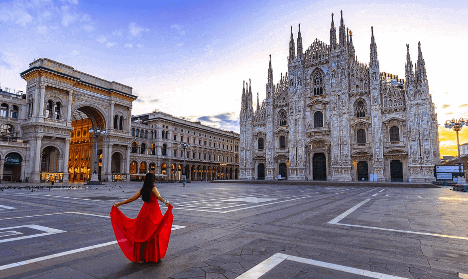 Woman dressed in a red dress facing the Milan Cathedral