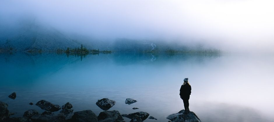 Girl standing on a rock next to a lake