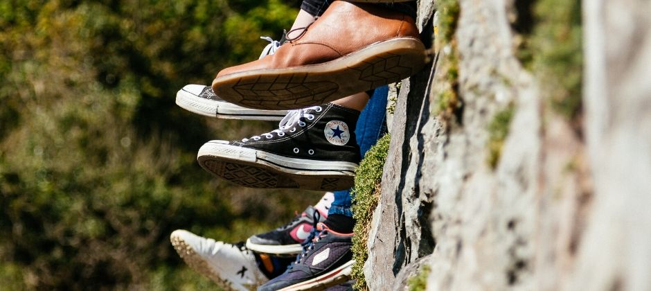 different shoes hanging over a stone wall