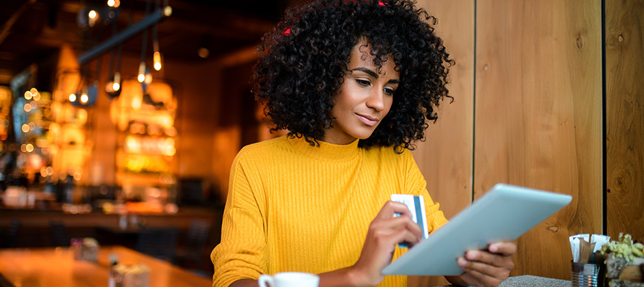 Kvinna som shoppar online på ett café