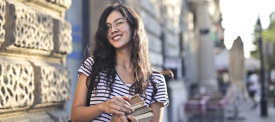 Kvinnlig student utanför skolbyggnad