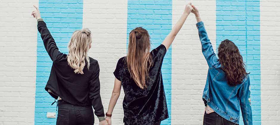 Tre tjejer står med ryggen mot kameran och håller varandra i handen