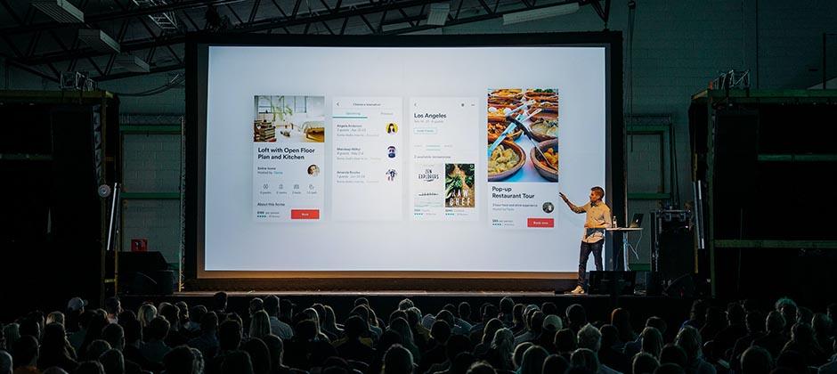 En kille står på en scen med en PowerPoint-presentation i bakgrunden