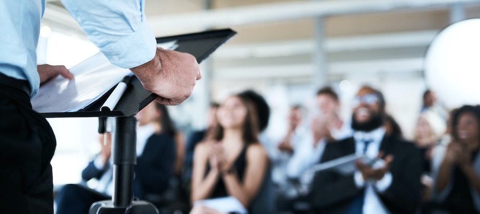 a man giving a presentation to a group of seated attendees