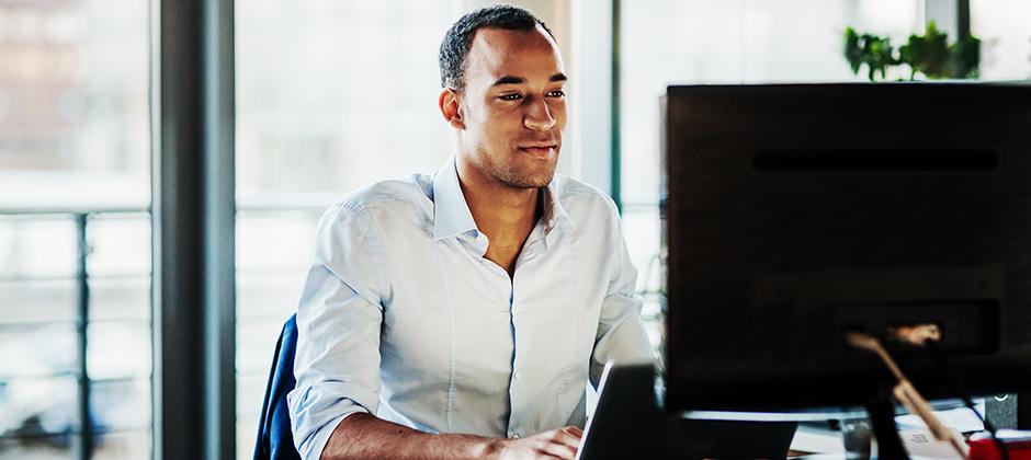 Mies istuu tietokoneen äärellä