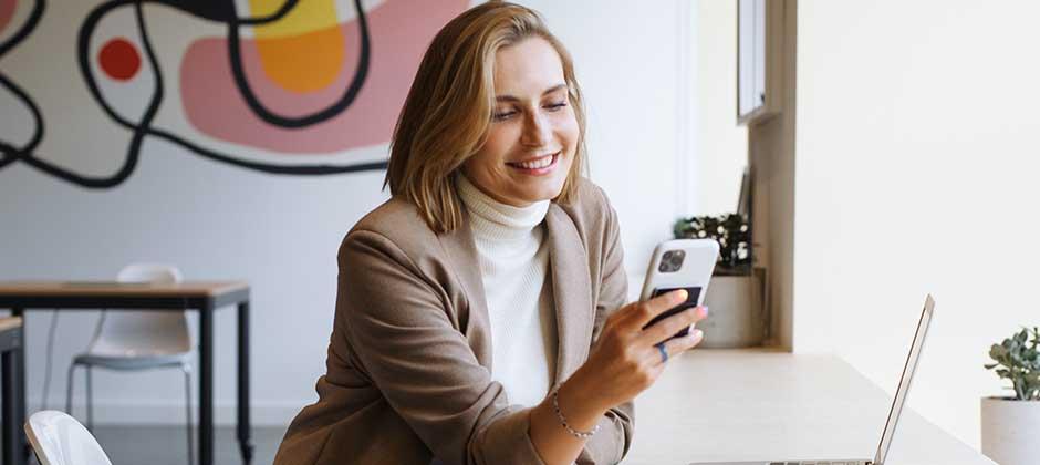 Ljushårig kvinna med smartphone och laptop