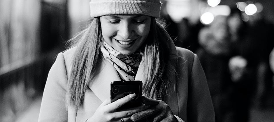 pipopäinen nainen hymyilee ja katsoo puhelintaan, mustavalkokuva