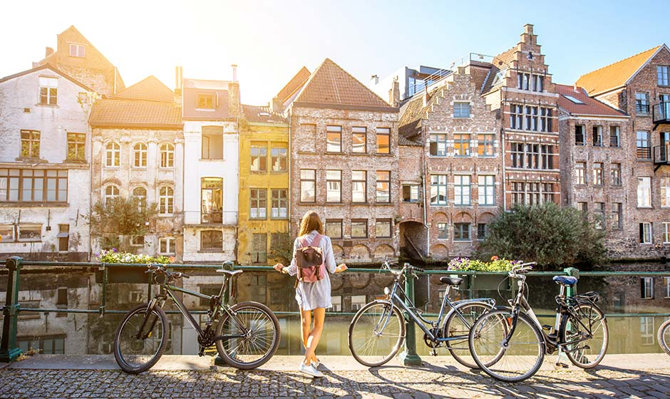 A student stands in front of buildings in Belgium
