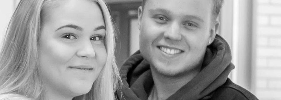 Kaksi henkilöä hymyilee, katse kamerassa.