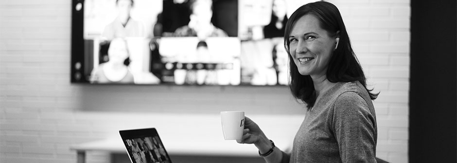 Hymyilevä nainen kahvikupin kanssa läppärin äärellä, mustaharmaa kuva
