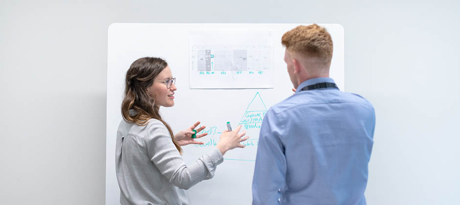 två projektledare vid en tavla