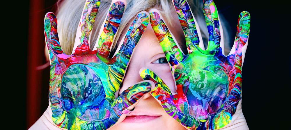 Ett barn med händerna fyllda med fingerfärg i olika färger. Barnet håller händerna framför ansiktet.