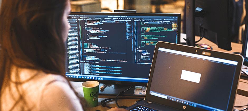 Kvinnlig programmerare framför laptop arbetar med robotprogrammering