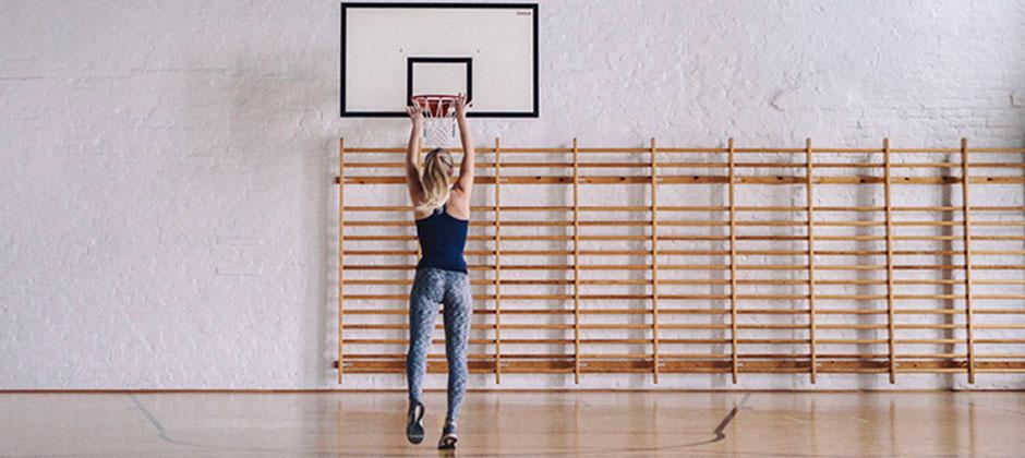 En person kastar en basketboll mot korgen i en gympasal