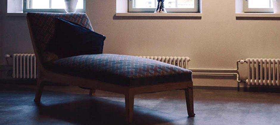En divan med en kudde i ett mörkt rum