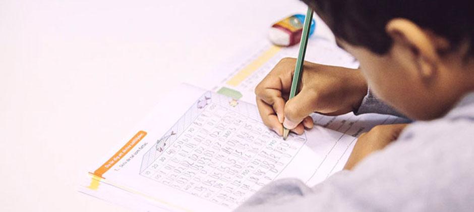 ett barn sitter i en skolbänk och skriver i en bok