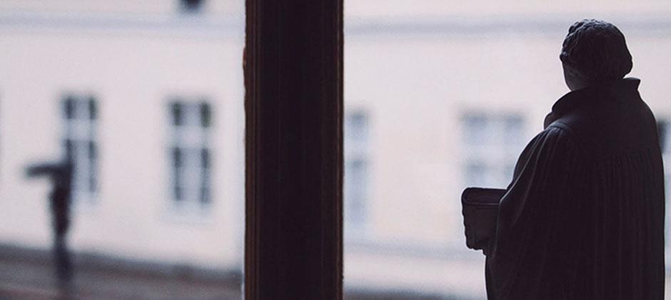 en staty som ser ut som en gammeldags präst blickar ut från ett fönster