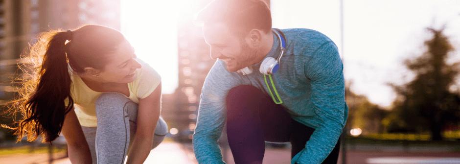 Kaksi hyvinvointivalmentajaa solmimassa lenkkareidennauhoja