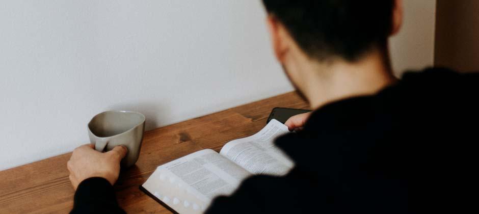 kille sitter och läser i en bok och dricker en kopp kaffe
