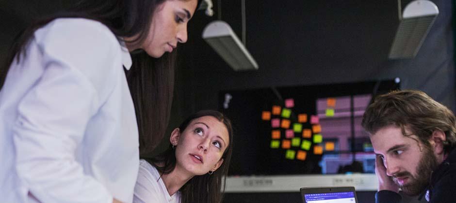tre studenter grupparbetar vid skärm