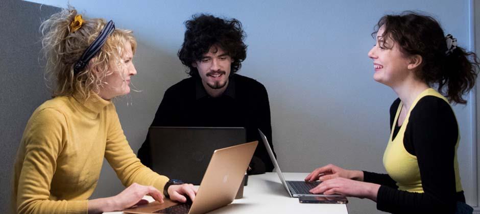 tre personer sitter runt bord med datorer