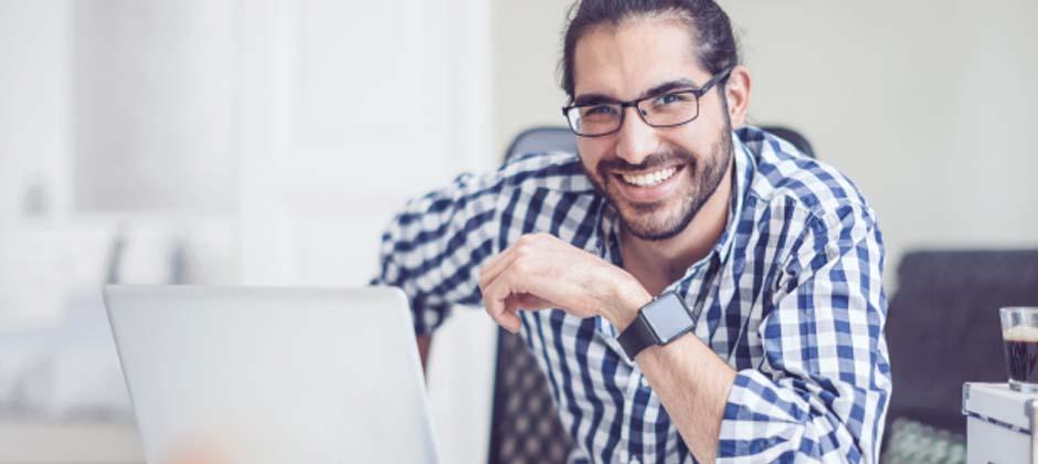 en man sitter framför en dator och ler