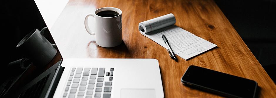 Pöydällä läppäri, kahvimuki, lehtiö ja älypuhelin
