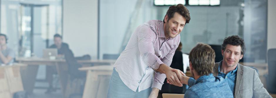 Kolme henkilöä toimistolla, joista yksi kättelee toista.