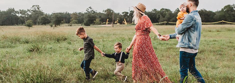 Perhe yhdessä peltomaisemassa käsi kädessä