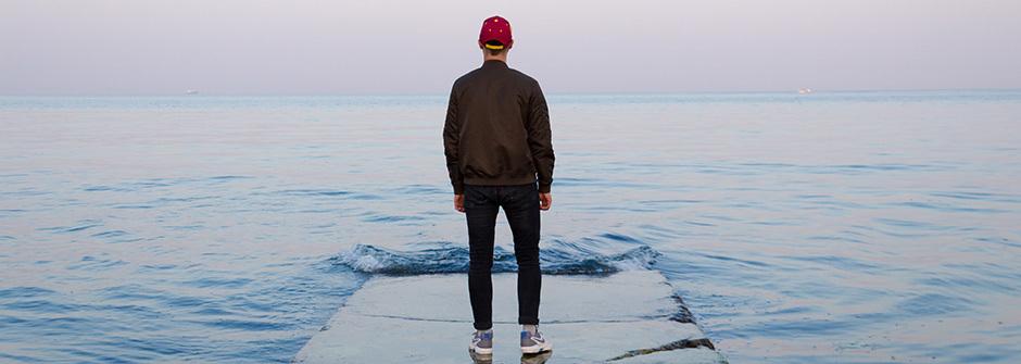 Henkilö katselee kauas merelle yksin