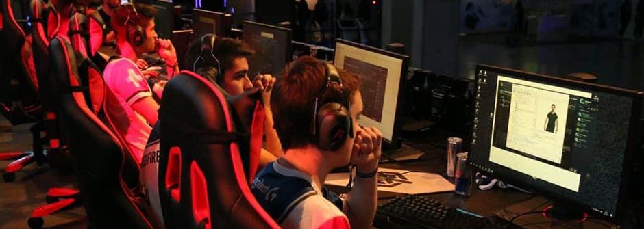 Pelaajat keskittyneinä tietokonepeliin kuulokkeet päässä