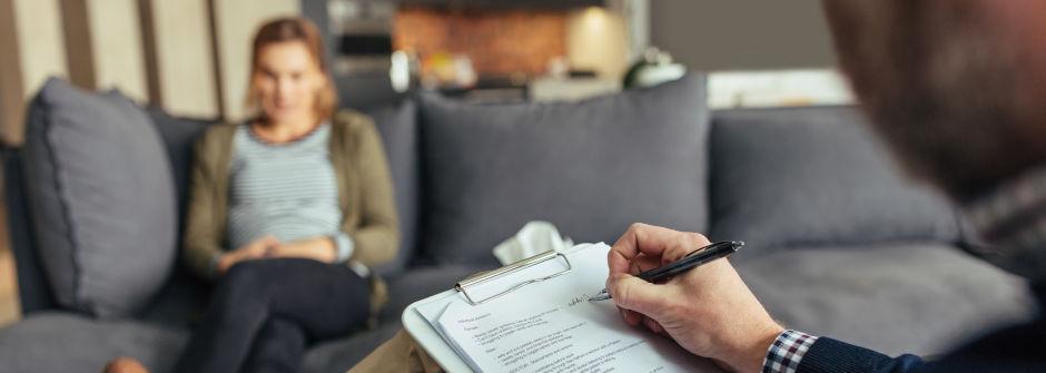 Henkilö istuu sohvalla, toinen kuuntelee ja kirjoittaa muistiinpanoja.