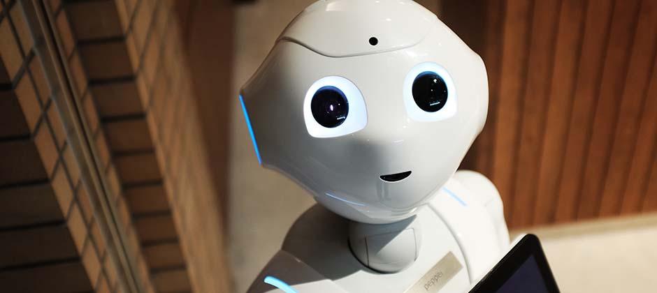 En vit robot lyser blått med en skylt på bröstet där det står Pepper