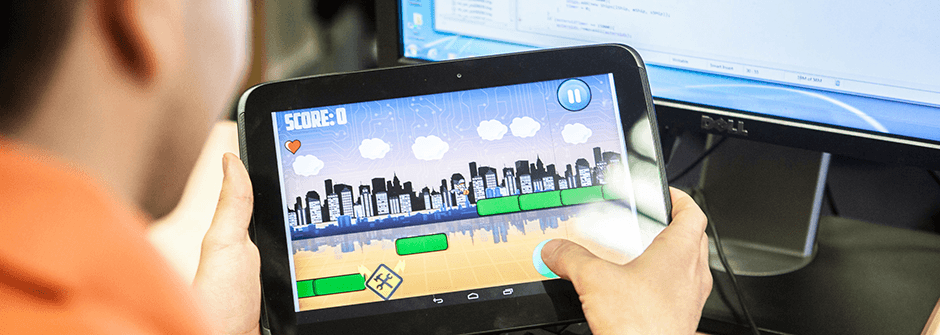 a person holding a tablet with a game on it, laptop with code in the background