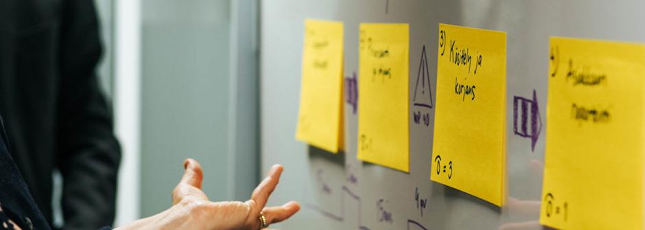 Kuvassa keltaisia post it -lappuja white boardilla