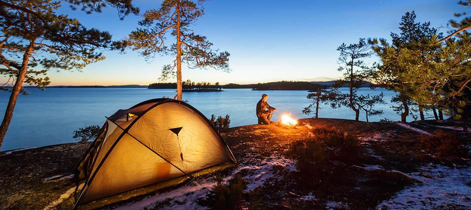 Friluftsliv med öppen eld och tältning vid vacker sjö.