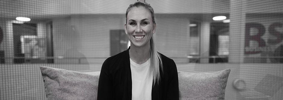 Nainen hymyilee läppärin ääressä (läppäri ei kuvassa, mutta etualalla), mustaharmaa kuva