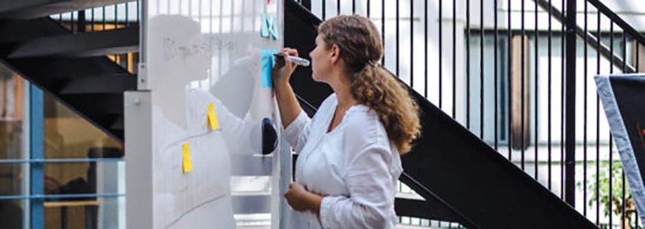 Kuvassa nainen ja whiteboard, jossa post it -lappuja