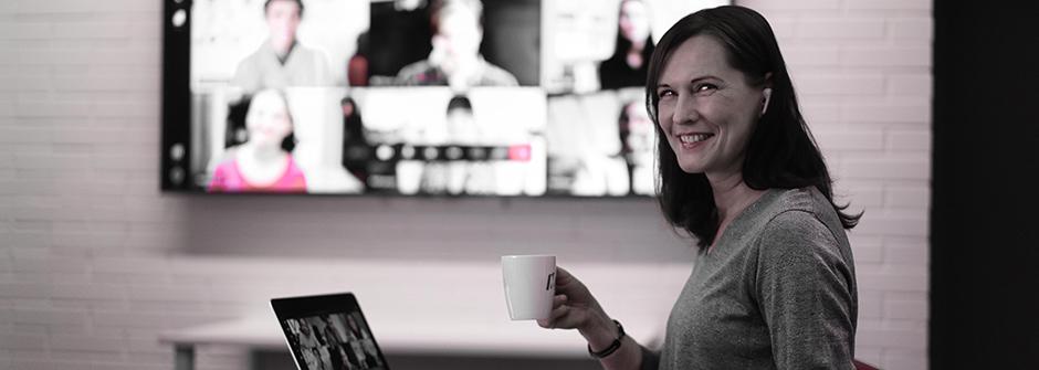 Hymyilevä nainen kahvikupin kanssa läppärin äärellä
