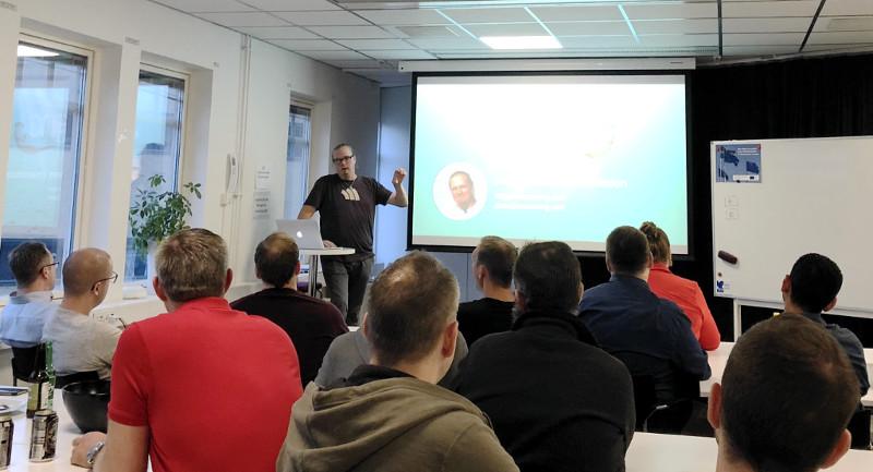 Jonas Schubert Erlandsson från Accodeing to you står i ett fullt konferensrum framför en projektorduk och föreläser
