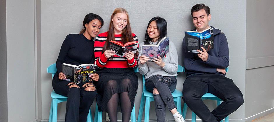 Elever som sitter tillsammans och läser böcker i korridor