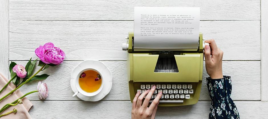 person framför en skrivmaskin med en kopp te bredvid
