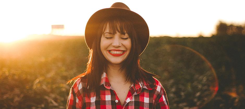 ung kvinna som står på en äng med solljus i bakgrunden