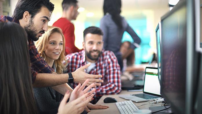 Människor runt dator som engagerat tittar på siffror