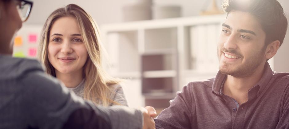 Personer i mötesrum förhandlar och skakar hand över ett bord
